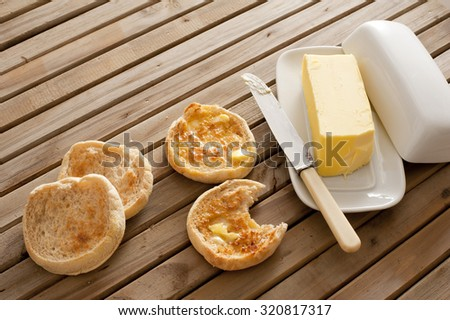 Fresh toasted hot English muffins, one with a bite missing, on a wooden slatted table with a pat of butter in a butter dish - stock photo