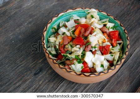 fresh tomato and cabbage salad with parsley in ceramic bowl on rustic wooden table - stock photo