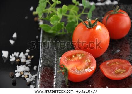 Fresh tomato and sliced tomato on black tray - stock photo