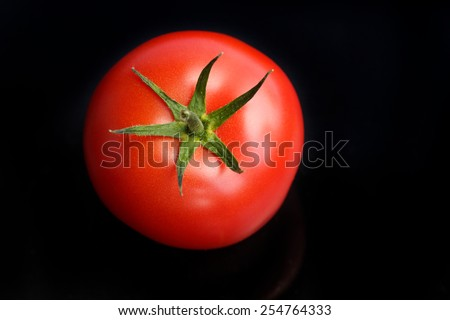 fresh tomato on black background - stock photo