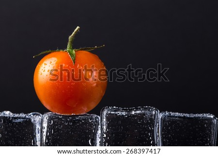 Fresh tomato on wet ice cubes on black background. Selective focus. - stock photo
