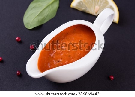 fresh tomato sauce in the white sauce boat - stock photo