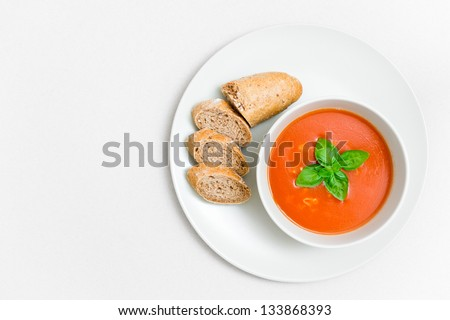 Fresh tomato soup with small bread and basil leaf on a plate with paper textured background - stock photo