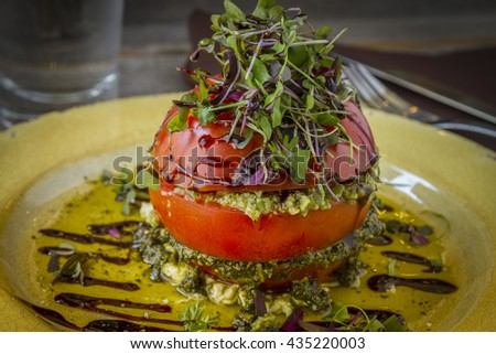 Fresh tomato tower filled with olive tapenade sitting on ricotta cheese, balsamic vinegar and olive oil and garnished with microgreens sitting on rustic yellow plate - stock photo