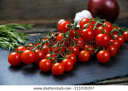 Fresh Tomatoes and Green Vegetables. Onion, Rosemary, garlic on on a stone board. - stock photo