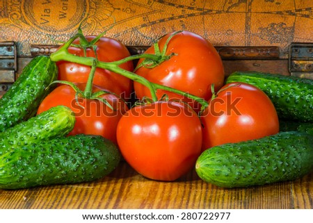Fresh tomatoes branch and cucumbers on old cutting board background. - stock photo