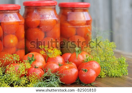 Fresh tomatoes. Canned tomatoes. tomatoes in a glass jar on a wooden table. - stock photo