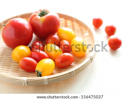 Fresh tomatoes in bamboo tray - stock photo