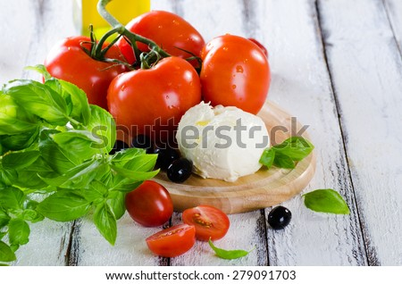 Fresh tomatoes, mozzarella and basil ingredients for salad on white wooden background - stock photo