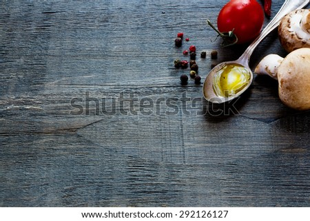 Fresh tomatoes, olive oil and mushrooms on dark wooden background with space for text. Vegetarian food, health or cooking concept. - stock photo