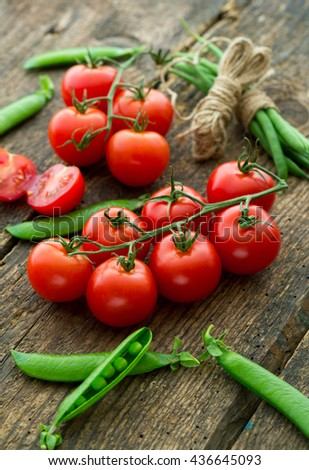 Fresh tomatoes with asparagus and green peas on a wooden background. Fresh organic vegetables. Food background. Healthy food from garden - stock photo