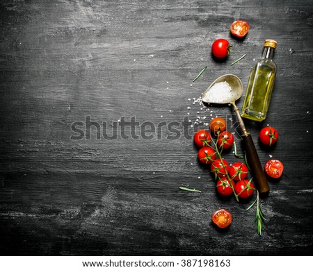 Fresh tomatoes with olive oil and a spoon of salt. On black rustic background. - stock photo