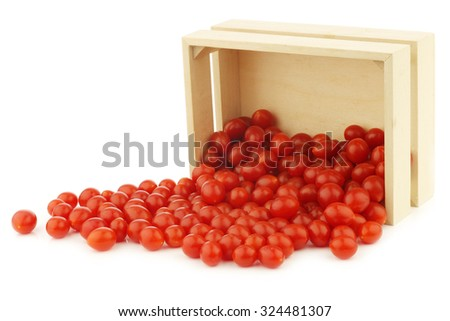 fresh Tomberry (very small) tomatoes in a wooden crate on a white background - stock photo