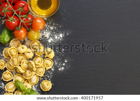Fresh tortellini pasta and ingredients on a dark board top view - stock photo