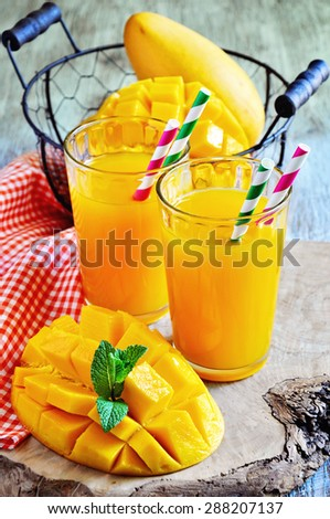 Fresh tropical mango drink and juicy mango fruits on wooden background. Selective focus. - stock photo