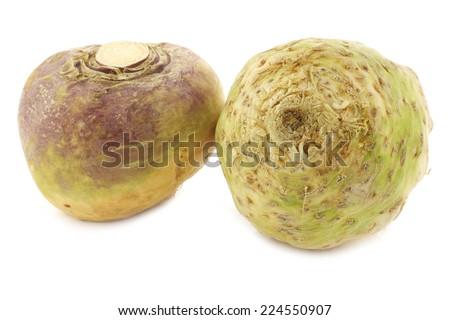 fresh turnip (Brassica rapa rapa) and a celery root(Apium graveolens var. rapaceum) on a white background - stock photo