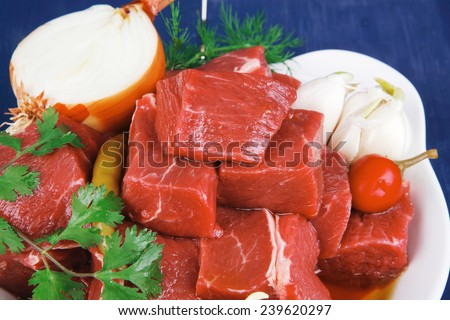 fresh uncooked beef meat slices over white bowls ready to prepare with red peppers and greenery serving on blue table with cutlery - stock photo