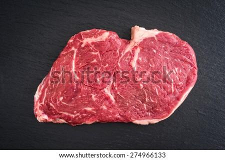 Fresh uncooked rib-eye steak on black background - stock photo