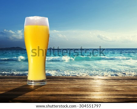 fresh  unfiltered beer and tropical beach - stock photo