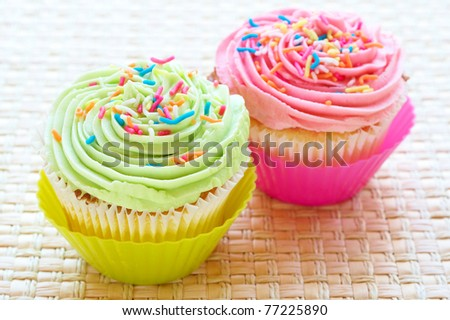 Fresh vanilla cupcakes with strawberry and lime icing on woven placemat background - stock photo