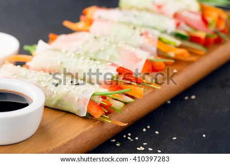 Fresh vegan spring rolls wrapped in rice paper with vegetables and green sauce on black stone background, selective focus - stock photo