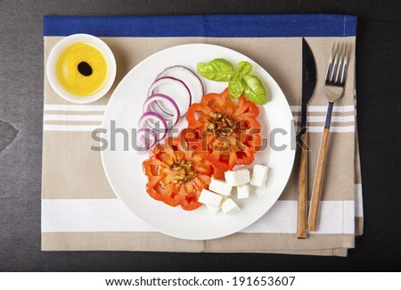 fresh vegetable greek salad. balsamic vinegar & olive oil. basil leaf. on a white plate and & colorful napkin. cooking ingredients. salad ingredients - stock photo