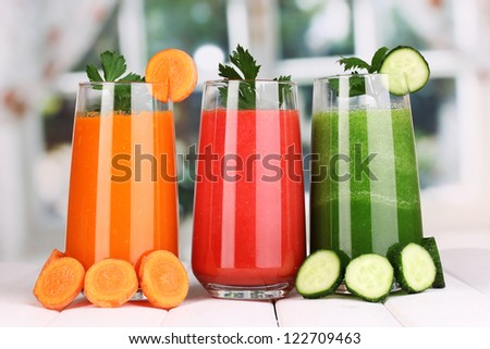 Fresh vegetable juices on wooden table, on window background - stock photo