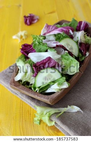 fresh vegetable salad in wooden bowl on yellow background - stock photo