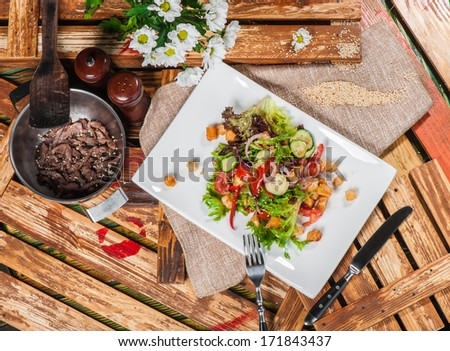 Fresh vegetable salad served with fried meat in pan - stock photo