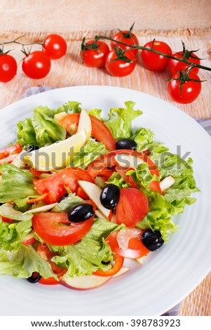 Fresh vegetable salad with apples, tomatoes, lettuce, celery and olives on the wooden table - stock photo