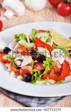 Fresh vegetable salad with mushrooms, apples, tomatoes, lettuce, celery and olives on the wooden table - stock photo