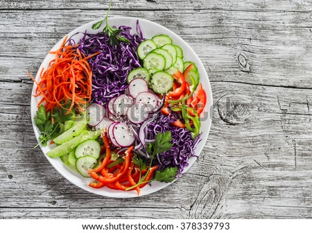 Fresh vegetable salad with red cabbage, cucumber, radish, carrots, sweet peppers, red onion and parsley on a white plate. Light on wooden rustic background - stock photo