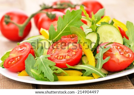 Fresh vegetable salad with tomatoes, rucola, cucumber and pepper - stock photo