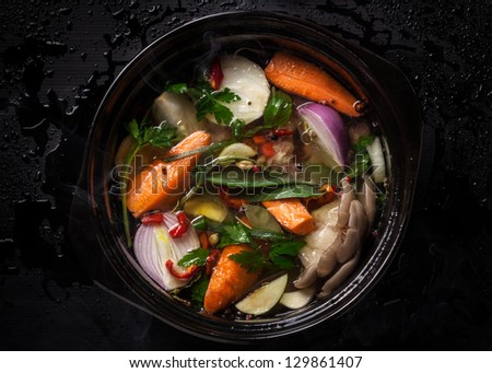 Fresh vegetable soup in a pot on black background - stock photo
