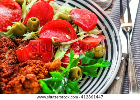 Fresh vegetable spring salad with tomato, green olives and parsley in white bowl on wooden table, closeup. - stock photo