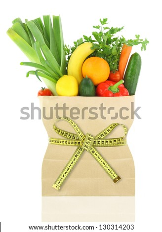Fresh vegetables and fruits in a paper grocery bag with measuring tape - stock photo