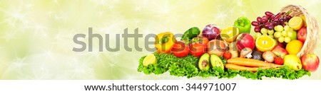 Fresh Vegetables and fruits over green background. Healthy diet. - stock photo