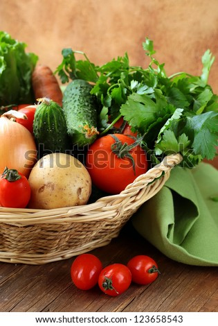 fresh vegetables and herbs mix in a wicker basket - stock photo