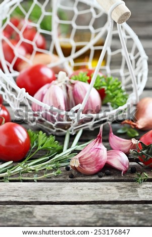 Fresh vegetables and herbs on a rustic wooden table. Selective focus. - stock photo