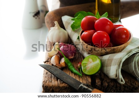 fresh vegetables and olive oil on an old weathered wood with a old mortar in behind over white background - stock photo