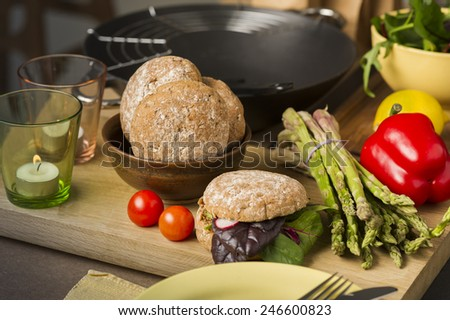 Fresh vegetables and rolls in a kitchen on a wooden counter with a bundle of fresh green asparagus tips, cherry tomatoes, red bell pepper lemon and leafy herbs for preparing salads and savory rolls - stock photo