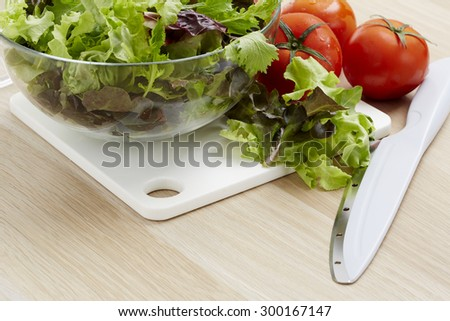 Fresh vegetables and salad ingredients on a wooden kitchen table. - stock photo