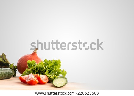 Fresh vegetables and salad ingredients standing ready for cooking on a wooden kitchen table in the bottom left corner of the frame with large copyspace on a grey background. - stock photo
