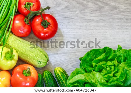 Fresh vegetables arranged around frame on grey wooden background. Flat lay with copy space - stock photo
