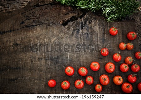 Fresh vegetables. Cherry tomatoes with rosemary on wood in vegetable garden - stock photo