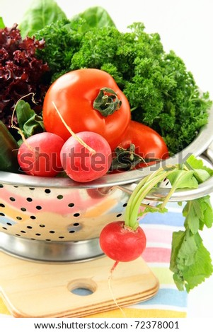 fresh vegetables, cucumber, radish, tomato and lettuce in a colander - stock photo