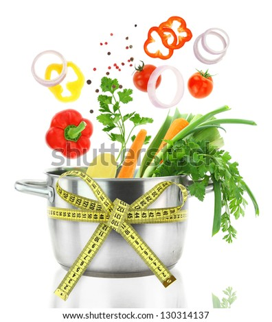 Fresh vegetables falling into a casserole pot with measuring tape - stock photo