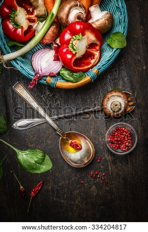 Fresh vegetables in basket, cooking spoons with oil and spices on rustic wooden background, top view. Vegetarian and Healthy food concept. - stock photo