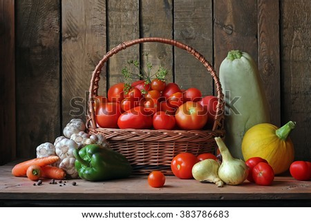 Fresh vegetables in basket on wooden table against the wall from boards. - stock photo