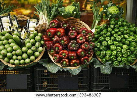 Fresh vegetables in baskets presented for sale above chalk board price tags on market.Bell pepper, italian pepper and green eggplants, onion, cabbage leaves and more - stock photo